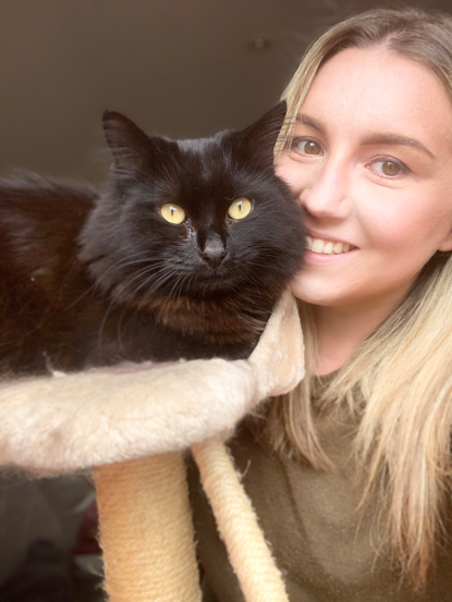 blonde woman with long-haired black cat