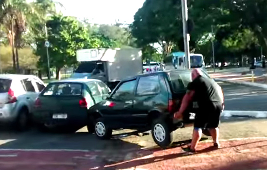 Homem levanta no braço carro que estava no meio da ciclovia