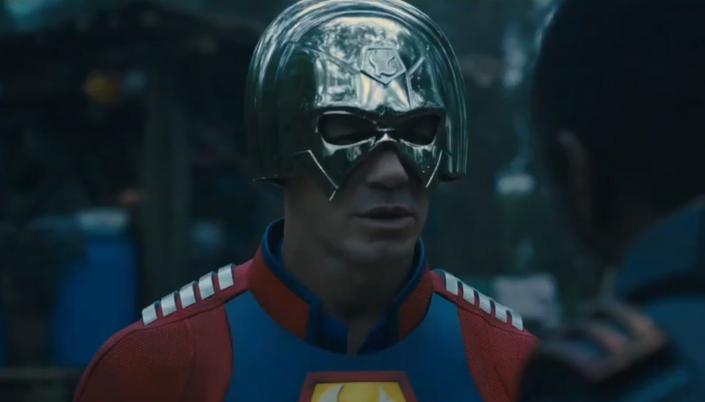 Imagem: o Pacificador, interpretado por John Cena, um homem branco musculoso em uma roupa vermelha com aplicações de metal nos ombros e um elmo metálico com a parte de cima formando um arco e cobrindo a parte de cima da cabeça do Pacificador.