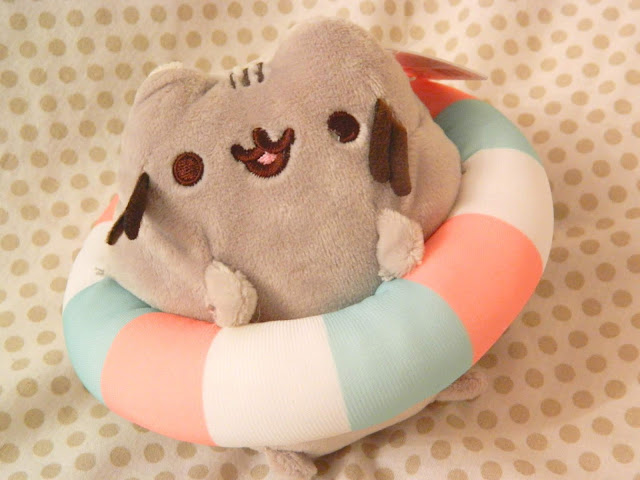 A plushie of Pusheen wearing a rubber ring for swimming