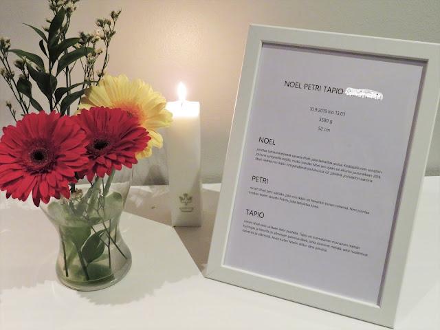 Lahjapöydässä oli nimitaulu, josta vieraat saivat lukea tarinat nimien takaaa. Kuvassa myös kasteessa saatu kynttilä ja isovanhemmilta saatu kukkakimppu