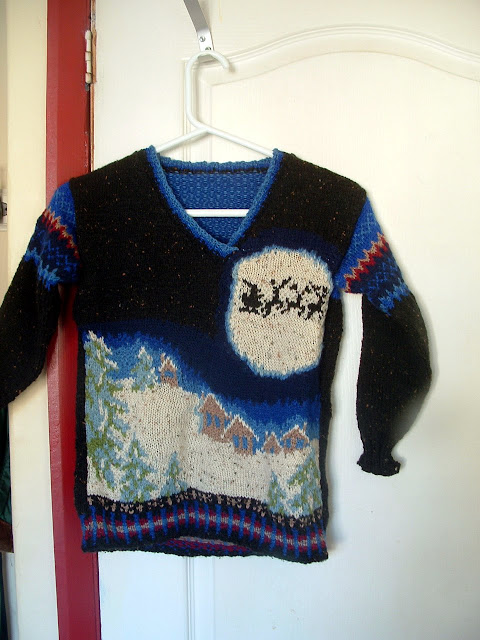 A hand knitted Christmas sweater showing a snowy village under the moon