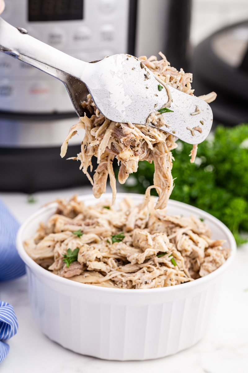 Instant Pot Shredded Chicken in a white bowl with a serving being help up with tongs.