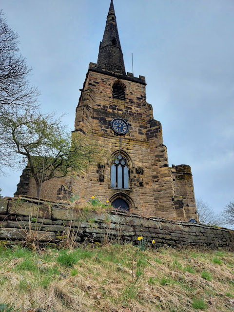 Winwick St Oswald's Church stands high above a walled grassy bank.  There are dark clouds behind the church spire