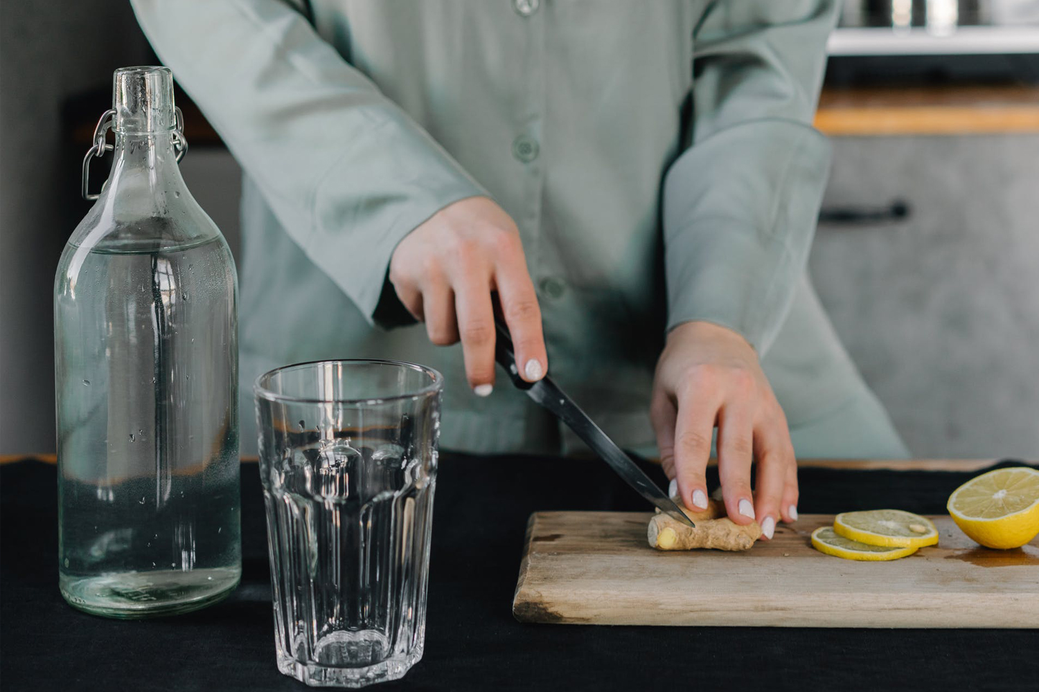 a woman dices lemon and ginger on a wooden cutting board