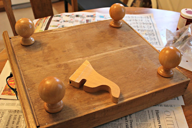 Photo of curtain rod finials being added as feet to a drawer bottom.