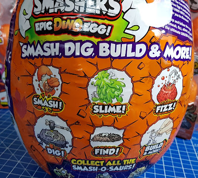 colourful illustration on the Smashers Epic Dino Egg packaging says smash slime fizz dig find build and more