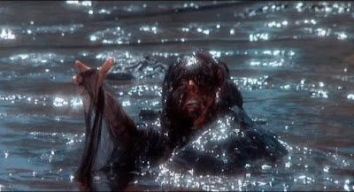 Creepshow 1987 horror movie still where a woman is eaten by a massive pile of swimming ooze in a lake