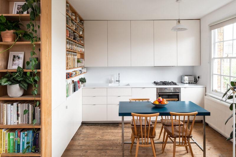 Cocina blanca y sin tiradores abierta al salón y con despensa