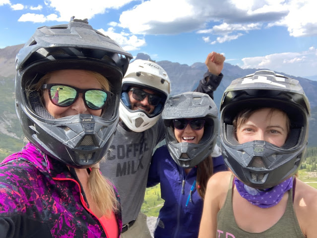 four people in the mountains wearing off-roading helmets