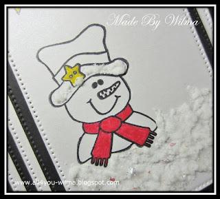 Close-up van de clearstempel van een sneeuwpop met hoge hoed en rode sjaal. Close-up of the clearstamp of a snowman with top hat and red scarf.