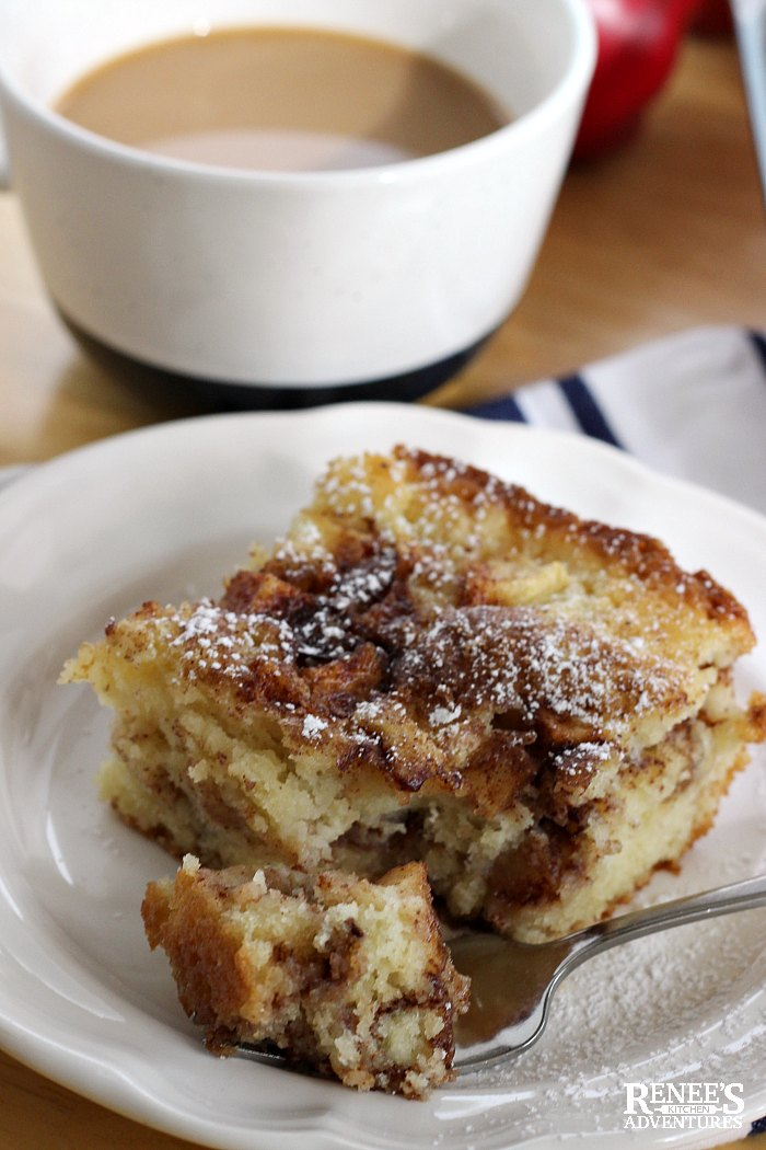 Apple Cinnamon Coffee Cake on plate with fork and a bite with a cup of coffee