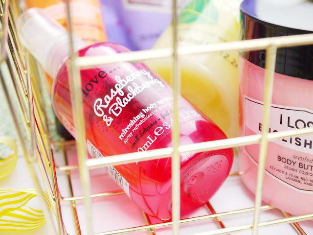 A hot pink bottle of I Love Raspberry and Blackberry body spray sat in a gold wire basket