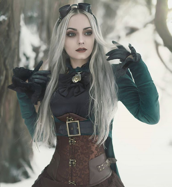 Steampunk girl in gothic victorian (Steamgoth) clothing in the middle of winter in a forest full of snow. women's steampunk clothing and fashion.