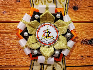 Close up shot of the orange and gold rosette ribbon lei for Philippine Coast Guard guest of honor