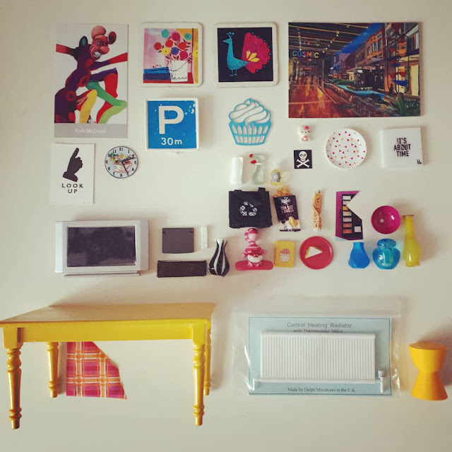 Flat lay of various one-twelfth scale modern miniatures in colours of yellow, teal and cerise including art works, a table, laptop, keyboard and monitor, several ornaments and various cleaning products.