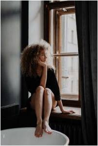 Woman sitting by the window thinking about energy efficient home upgrades that pay for themselves.