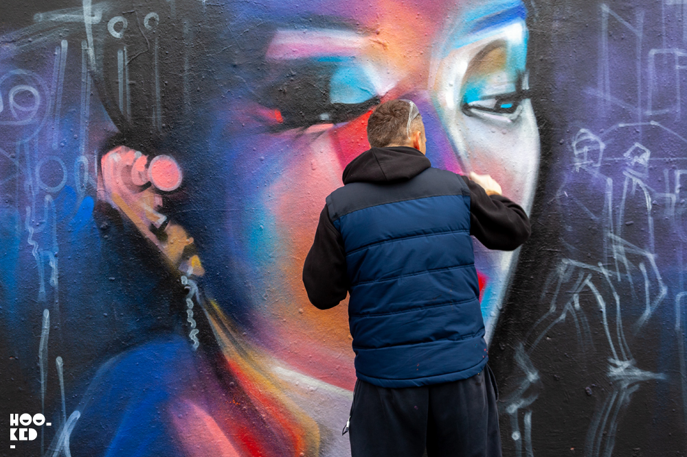 Street artist San Kitcheners at work on his new ghost cities mural in Shoreditch, London