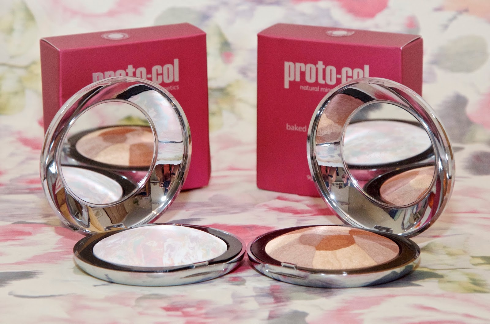 Baked Mineral Color Corrector and Baked Mineral Shimmer powder compacts on a pink floral paper