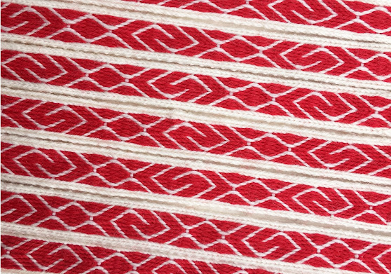 A photo of a red and white tablet woven band with S and Z motifs