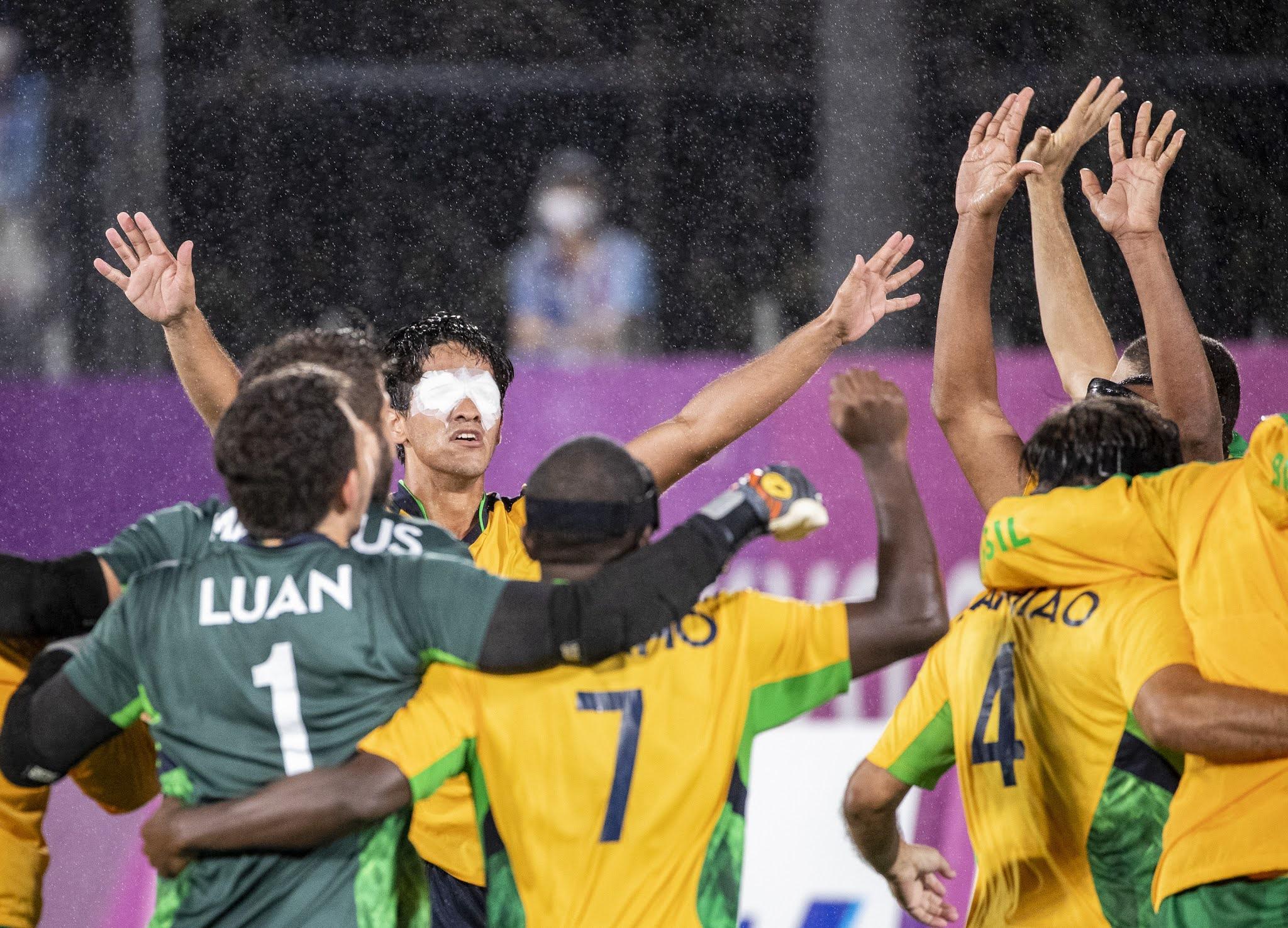 Os jogadores de linha, vestidos de amarelo, mais os goleiros, vestidos de verde, se abraçam debaixo de chuva para comemorar a conquista