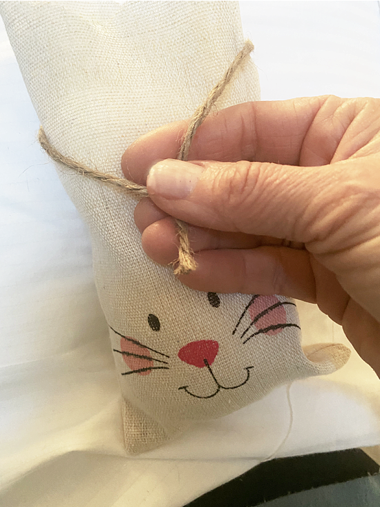 stuffed bunny with a knot tied with jute