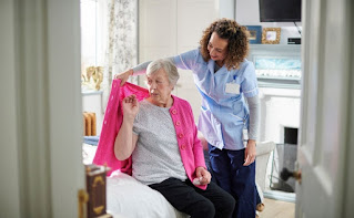 Fotografía de una cuidadora atendiendo a una persona mayor