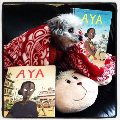 A tiny grey poodle, Murchie, stands on a sheep-shaped pillow. He wears an orange t-shirt and has a red and white blanket draped over him. Hardcover copies of Aya and Aya of Yop City are propped up on either side of him. Both books' covers feature the same young black woman standing in a city street. She has braided hair, and on one cover she carries a baby on her back.