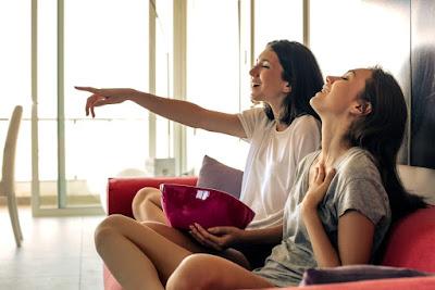 dve-devojke-gledaju-zajedno-televiziju-kokice-smeh