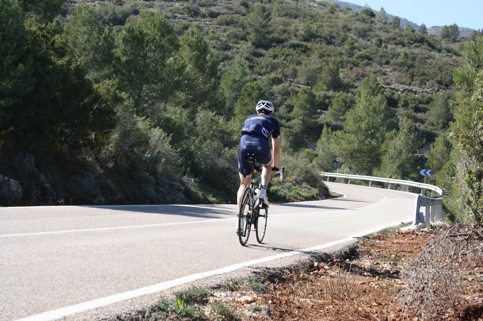 Cyclist climbing Coll de Rates from Parcent