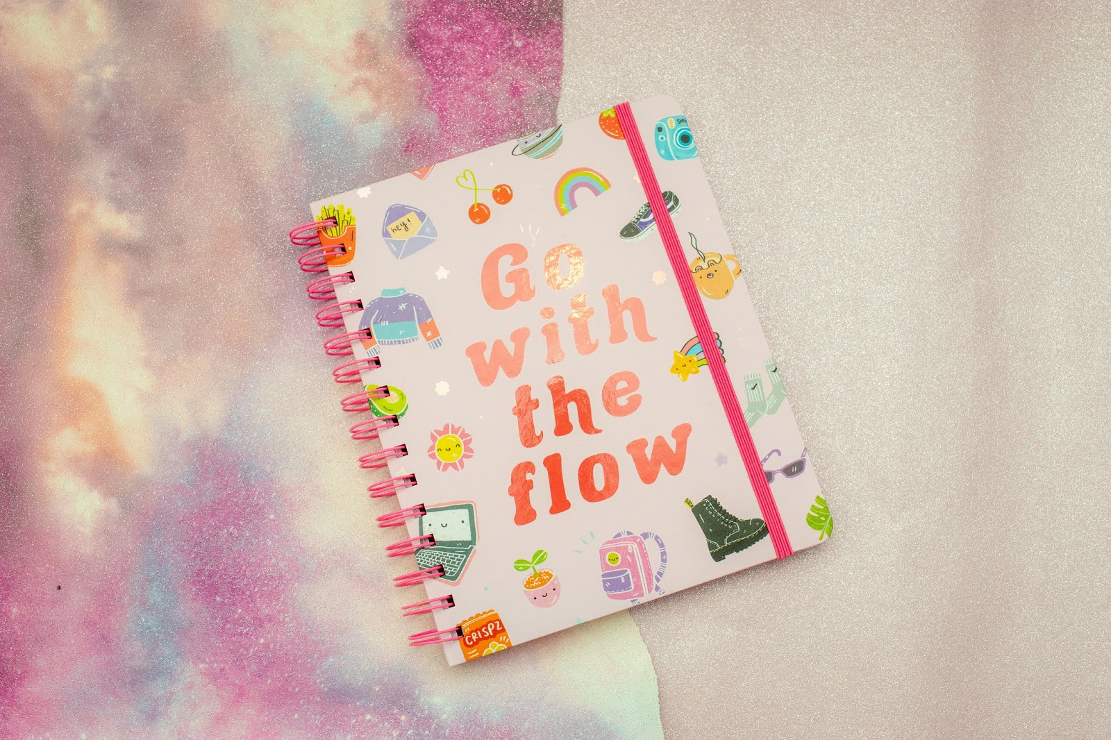 A spiral bound notebook with doodles on the front cover and the phrase: 'go with the flow' on the front in red letters.