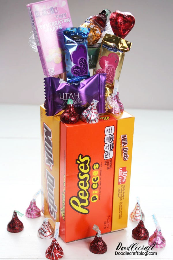 """Stick the wooden skewer """"flowers"""" into the stryofoam at the base of the candy bouquet vase. Then fill the inside of the vase with a sweet treat like kisses and hugs. Finish it off by taping some kisses around the top of the candy bouquet vase.  Now it just needs a """"happy Valentine's day"""" gift tag for your friend!"""
