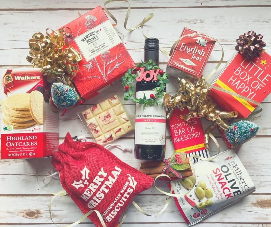 A hamper from prestige hampers - containing a bottle of red wine, shortbread biscuits, Highland oatcakes, white chocolate, cookies, olives, a chocolate bar, 20 English Tea bags, and chocolate covered marshmallows.
