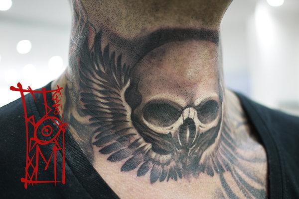 tatuaje en el cuello de calavera alada