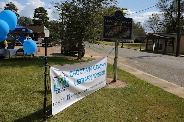 Outdoor moveable sign reads Choctaw County Library System, established 2017. Blue balloons are attached to the sign. A permanent marker for the Choctaw County Blues stands next to the sign.