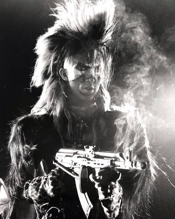 Martin Degville of Sigue Sigue Sputnik discharges an AK47 at Journalists after an unfavourable press review. Probably.