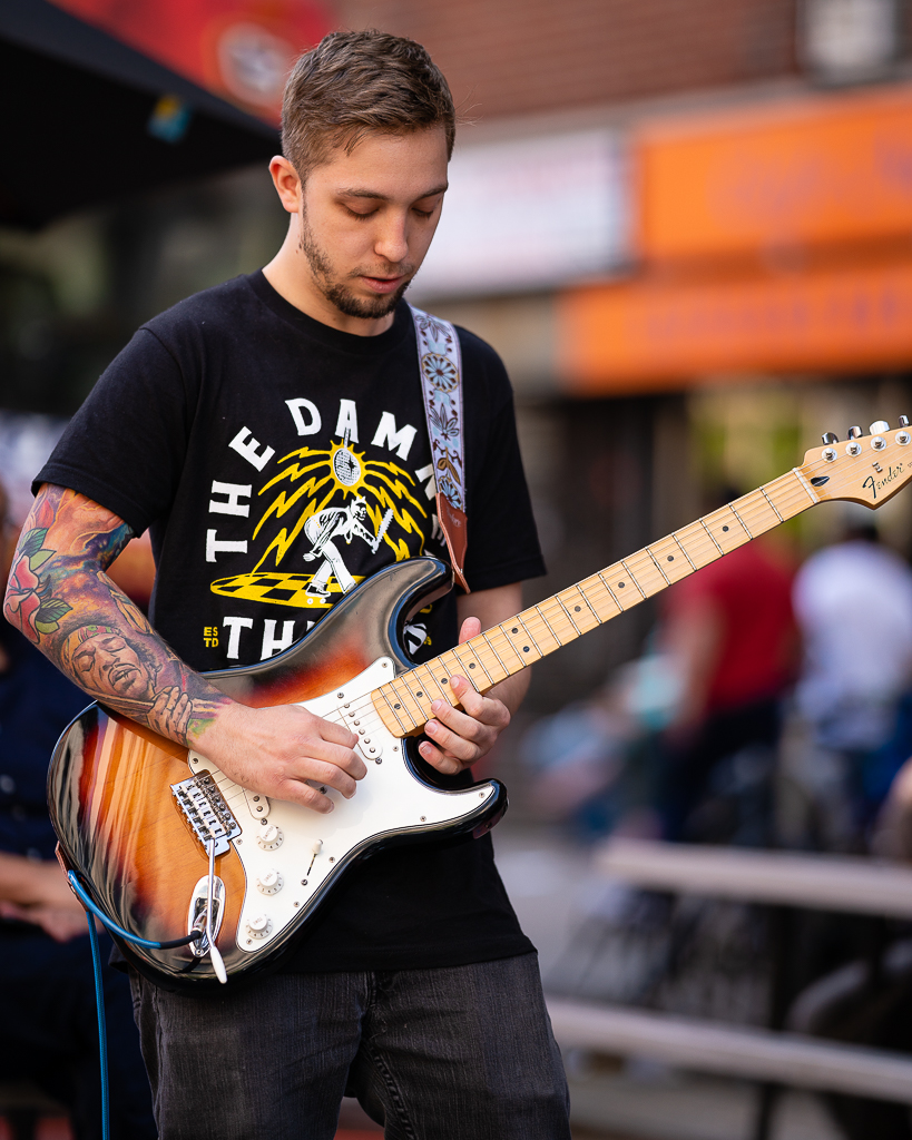 a guitarist with a tattoo of jimi hendrix plays a fender stratocaster in new york