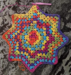 Work in progress shot of rainbow crochet star blanket.