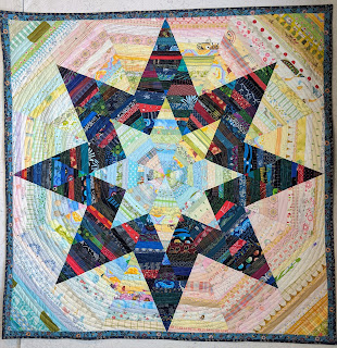Diamonds of dark or light strings are sewn into eight pointed stars with a light center and a dark outline