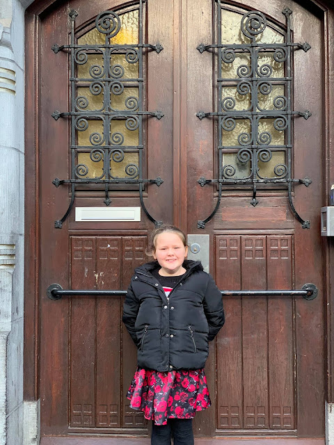Tilly standing in front of a door