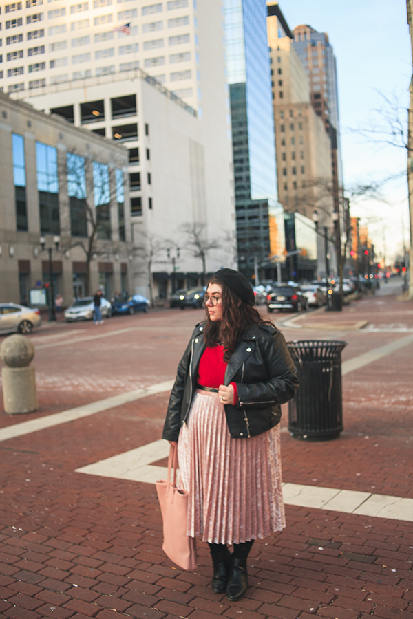 An outfit of black beret, black faux leather moto jacket, peter pan collared berry paisley dress, red sweater, pink velvet midi skirt, black tights with red hearts ala polka dots, black heeled chelsea boots and pink tote bag.
