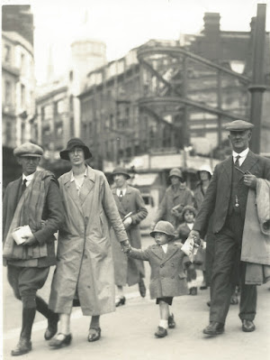 A couple with child and another gentleman walking down a city street