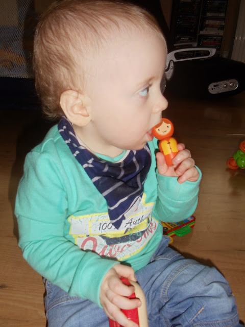 little boy holding a small wooden toy to his mouth