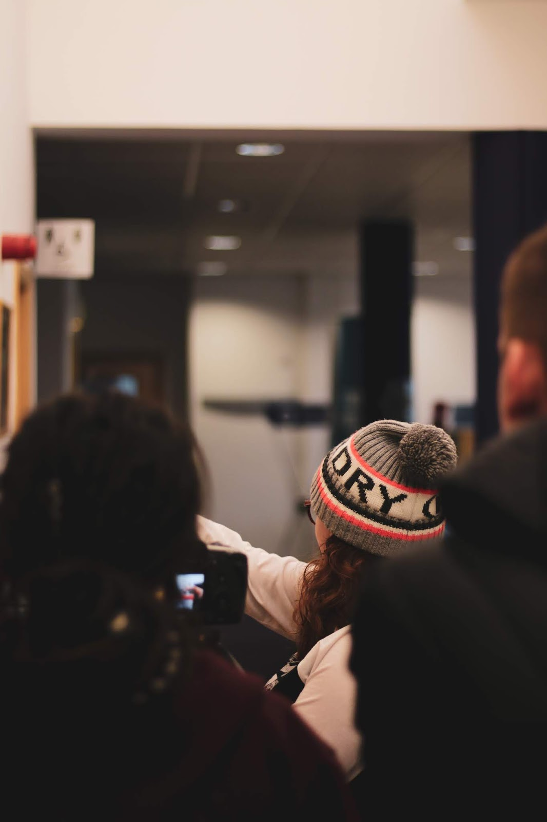 an over the shoulder shot by myself, Jordanne Lee. Two girls standing talking about the film project. the girl on the right has a super dry hat  on, glasses and a white top. The girl on the left has dreadlocks and is looking through a camera