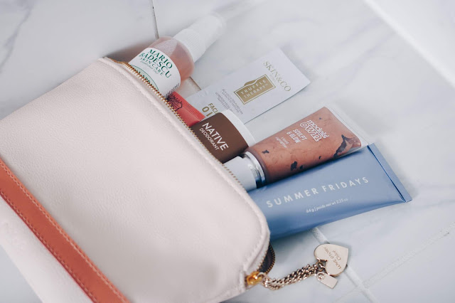 makeup bag with products on marble background