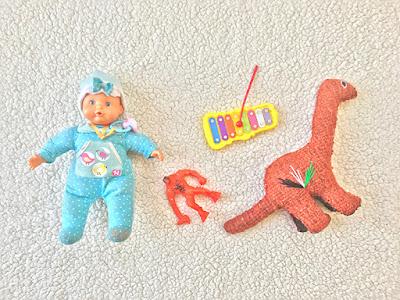 una muñeca vestida de azul, un dinosaurio de tela, un mounstro de plástico y un instrumento musical sobre una alfombra blanca