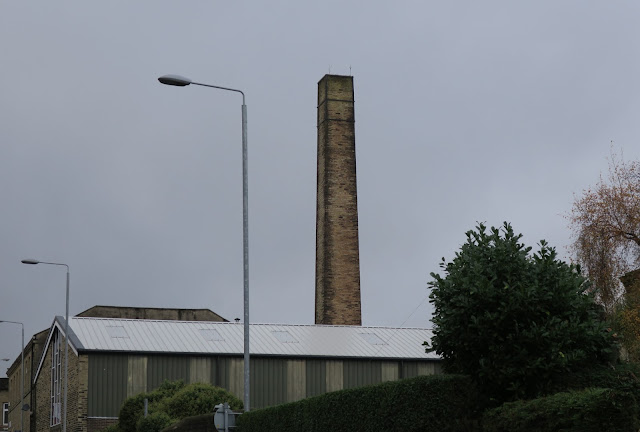 Chimney, buildings and street lights against a blank sky