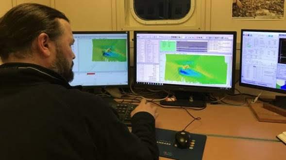 Figura 2. El técnico Ben Powell observa las imágenes generadas con sonar a bordo de la embarcación empleada en la exploración.