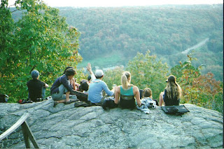 Photo of a family sitting together on a rock