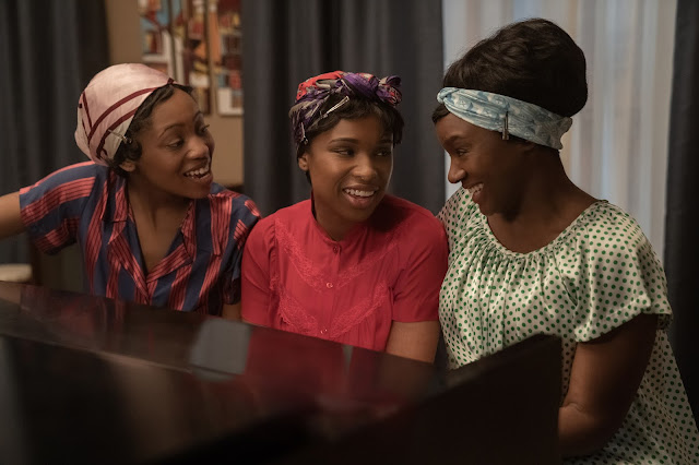 Three Black women play around a piano in night clothes